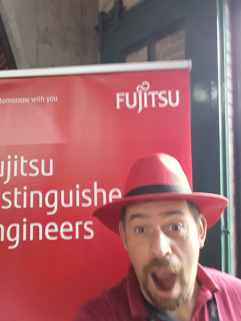 Jon in a Red Hat from RedHat standing in front of the Fujitsu Distinguished Engineers banner